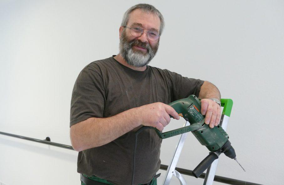 Diakos Hausmeister auf Leiter mit Bohrmaschine