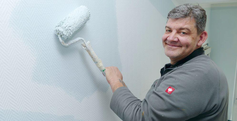 Maler streicht Wand mit weißer Farbe
