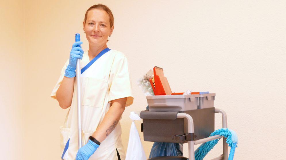 Frau mit Reinigungswagen und Besen