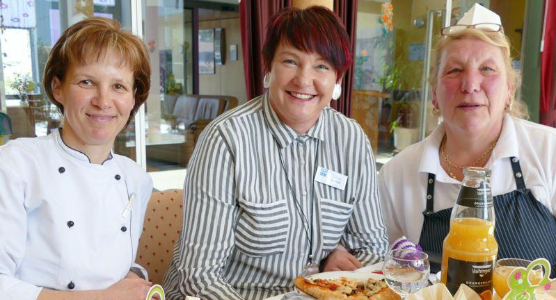 3 Kolleginnen im Diakonie-Altenpflegeheim sitzen gemeinsam am Tisch
