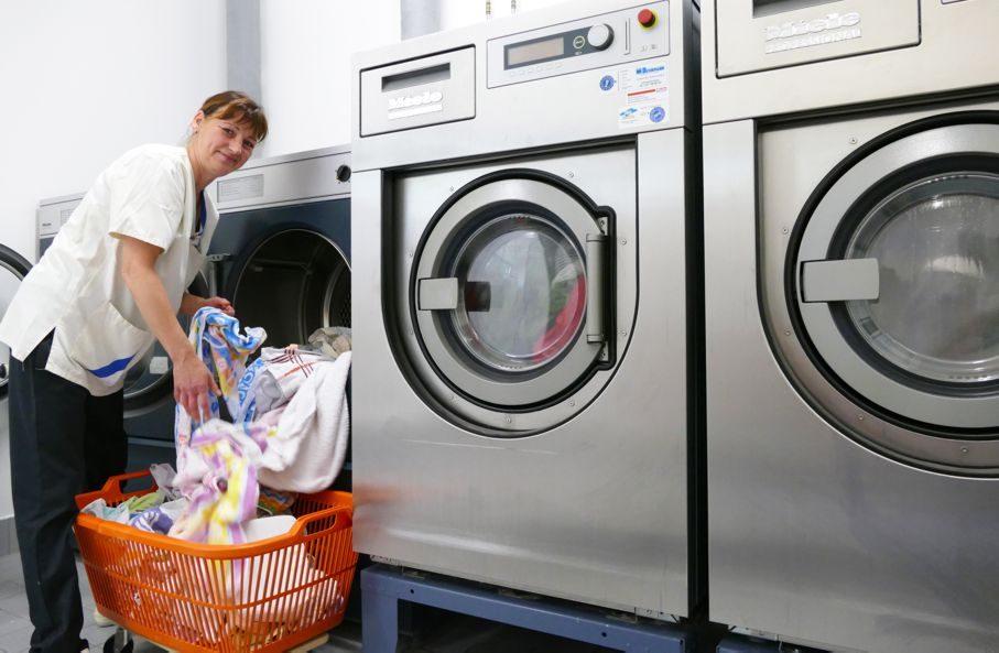 Frau nimmt Wäsche aus Industriewaschmaschine